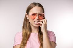 Worried Caucasian woman in stylish T-shirt biting her fingers. Close up portrait.bad emotions, feelings concepts stock images
