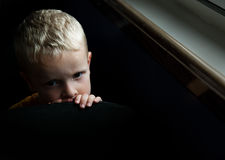 Worried Child. Sad?  Scared? Worried?  Emotional black image of a young child.  Child was actually just tired... but the lighting really evokes emotion.  It Royalty Free Stock Image