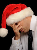 Worried Christmas businessman. A worried businessman wearing a santa hat, on black studio background Royalty Free Stock Photos