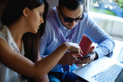 Worried colleagues looking at mobile phone Royalty Free Stock Images