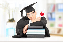 Worried college graduate leaning on stack of books, indoors Royalty Free Stock Photos
