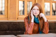 Worried concerned woman talking on cellphone in outdoor cafe. Worried concerned young redhead woman in leather jacket and scarf talking on cellphone in outdoor Stock Photography