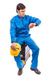 Worried construction worker looking at watch with serious expre Royalty Free Stock Image