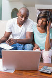 Worried couple calculating bills on the couch Stock Images