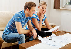 Worried couple calculating bills at home Stock Photos
