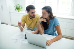 Worried couple calculating their bills with laptop in the kitchen. At home stock photo