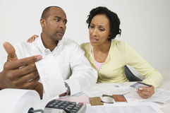 Worried Couple With Expense Receipt And Credit Cards Stock Image