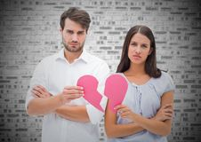 Worried couple holding a broken heart Stock Image