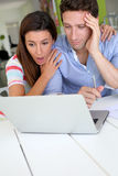 Worried couple at home looking at news on laptop stock photo