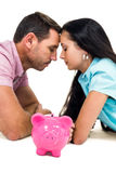 Worried couple laying on the floor face to face with piggybank Stock Photo