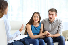 Worried couple listening to marriage counselor. During a therapy sitting on a sofa at home Royalty Free Stock Photos