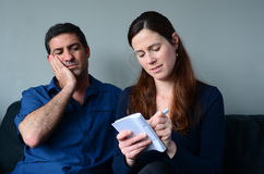 Worried couple listing expenses Stock Image