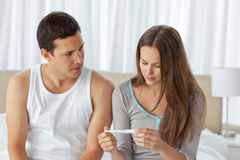 Worried couple looking at a pregnancy test. Sitting on their bed at home Stock Photography