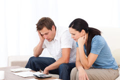 Worried couple looking at their bills on the sofa Stock Image