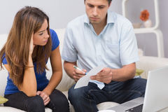 Worried couple paying bills online with laptop at home Royalty Free Stock Images