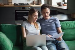 Worried couple reading documents or calculating high domestic bi. Worried couple confused reading bad news in bank loan documents or money debt calculating high royalty free stock photo