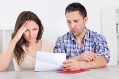 Worried couple reading paper Stock Photo