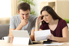 Worried couple reading together a letter. Sitting in a desk at home Stock Photography