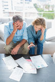 Worried couple sitting on their couch paying their bills Stock Photos