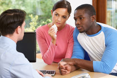 Worried Couple Talking With Financial Advisor In Office Stock Photo