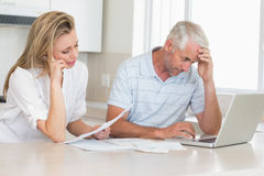 Worried couple working out their finances with laptop Royalty Free Stock Images