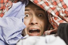 Frustrated young man with full of clothes on his head. Laundry time. Worried and crying young man before laundry. He has enough housekeeping stock image
