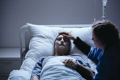 Worried daughter taking care of weak elderly mother with cancer. In hospital stock images