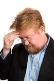 Worried Depressed Mature Man. Worried and depressed mature businessman with red hair  holds his forehead in thought Stock Photography