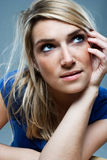 Worried depressed woman. Worried depressed attractive blond woman with disheveled blond hair and a sombre expression sitting looking up into the air in Royalty Free Stock Images