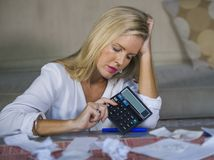 Worried and desperate blond woman calculating domestic money exp. Attractive worried and desperate blond woman calculating domestic money expenses doing royalty free stock image