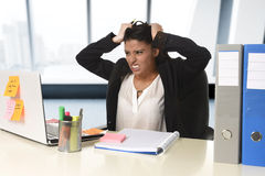 Worried and desperate businesswoman suffering stress working at office computer desk Stock Photography