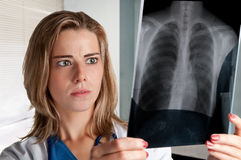 Worried Doctor. Worried female doctor looking at an x-ray Royalty Free Stock Photo