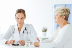 Worried doctor during patient`s visit. Worried doctor looking at bad results of medical examinations during patient`s visit Stock Photos
