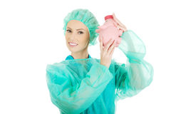 Worried doctor with pink piggy bank. Stock Photo