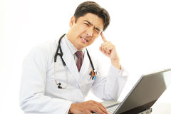 Worried doctor. Portrait of an overworked and tired Asian doctor Royalty Free Stock Images
