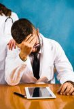 Worried doctor showing concern on the table. Worried doctor showing concern and regret on the table royalty free stock photo