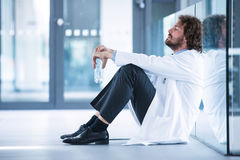 Worried doctor sitting on floor Stock Images