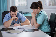 Worried doctors reading medical records Royalty Free Stock Image