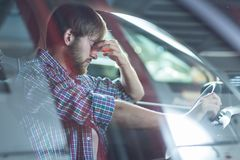 Worried driver in his car. Image of worried driver sitting in his car at workshop Royalty Free Stock Images
