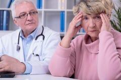 Worried elder woman. Elder women is worried because of her malady Stock Image
