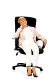 Worried elderly business woman sitting on armchair Stock Photo