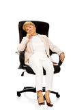 Worried elderly business woman sitting on armchair Stock Photos