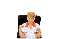 Worried elderly female doctor or nurse sitting behind the desk and holds two pair of glasses Stock Photography