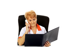 Worried elderly female doctor or nurse sitting behind the desk and talking through a phone Stock Images