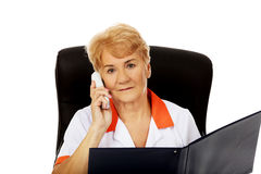 Worried elderly female doctor or nurse sitting behind the desk and talking through a phone Royalty Free Stock Images