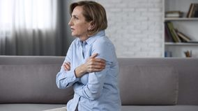 Worried elderly female sitting on couch, feeling anxious, psychological problems stock image