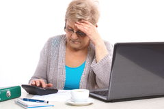 Worried elderly senior woman counting utility bills at her home, financial security in old age Stock Photo