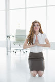 Worried elegant businesswoman joining hands in office Royalty Free Stock Images