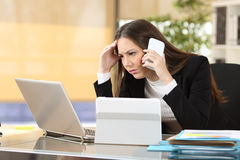 Worried executive with multiple devices Royalty Free Stock Images