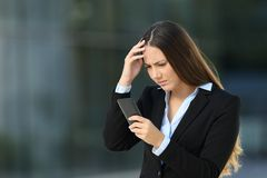 Worried executive reading bad news in a cellphone. On the street with an office building in the background royalty free stock images
